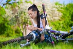 La muchacha se cayó de la bici en un parque verde imágenes de archivo libres de regalías