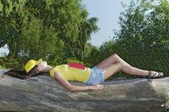 La muchacha se cayó dormido con un libro Fotos de archivo