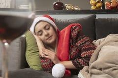 La muchacha se cayó dormido en el sofá, esperando la Navidad imagenes de archivo