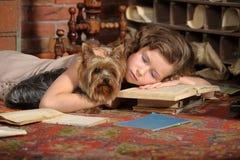 La muchacha se cayó dormido entre los libros Foto de archivo libre de regalías