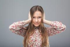 La muchacha se cierra los oídos con las manos Imagen de archivo libre de regalías