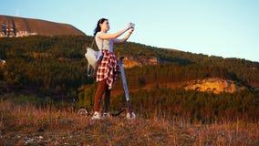 La muchacha se coloca al lado de la vespa eléctrica que toma las imágenes del paisaje y de la puesta del sol, vista posterior MES almacen de video