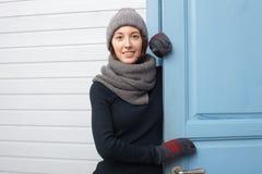 La muchacha se coloca cerca de puerta azul en invierno Foto de archivo libre de regalías