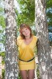 La muchacha se coloca cerca a un abedul Fotos de archivo libres de regalías