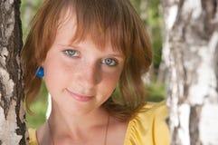 La muchacha se coloca cerca a un abedul Foto de archivo