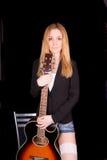 La muchacha se coloca con la guitarra Imágenes de archivo libres de regalías