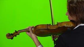 La muchacha se coloca con su parte posterior y toca el violín Pantalla verde Visión posterior Cierre para arriba almacen de metraje de vídeo