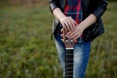 La muchacha se coloca con una guitarra sin jugar, secuencias en descanso, endecha Fotos de archivo libres de regalías