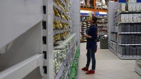 La muchacha se coloca delante del estante en la tienda almacen de video