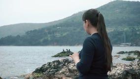 La muchacha se coloca en la costa rocosa del mar que mira la tableta y que admira las hermosas vistas y los paisajes metrajes