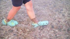 La muchacha se coloca en el agua en zapatos especiales, eso no cortaría sus piernas sobre muchas cáscaras y corales metrajes