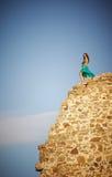 La muchacha se coloca en el borde de una pared de piedra vieja. Fotos de archivo libres de regalías