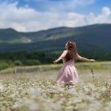 La muchacha se coloca en el prado de la manzanilla, vista posterior Fotos de archivo libres de regalías