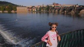 La muchacha se coloca en el puente en el fondo de Praga metrajes