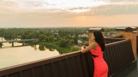 La muchacha se coloca en el tejado de una casa La puesta del sol imagenes de archivo
