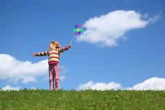 La muchacha se coloca en hierba y sostiene el molino de viento Fotografía de archivo