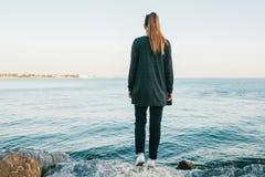 La muchacha se coloca en las rocas en la costa del Bosphorus y mira en la distancia y los sueños Visión desde la parte posterior Imagen de archivo