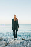 La muchacha se coloca en las rocas en la costa del Bosphorus y mira en la distancia y los sueños Visión desde la parte posterior Fotos de archivo