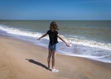 La muchacha se coloca en la orilla del océano con los brazos abiertos, haciendo frente al agua en Phuket, Tailandia Libertad, con Fotografía de archivo libre de regalías