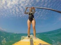 La muchacha se coloca para arriba que practica surf foto de archivo