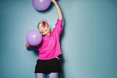 La muchacha se divierte con los globos coloreados en fondo azul Foto de archivo libre de regalías