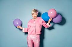 La muchacha se divierte con los globos coloreados en fondo azul Foto de archivo