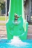 La muchacha se divierte en diapositiva de agua Foto de archivo