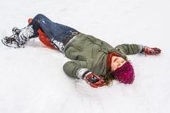 La muchacha se divierte que juega en la nieve Imagen de archivo libre de regalías