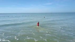 La muchacha se divierte que salpica con la agua de mar contra las boyas