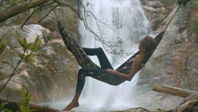 La muchacha se eleva en aire en la hamaca cerca de la cascada espumosa