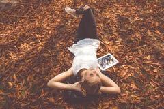 La muchacha se está acostando con la tableta digital al aire libre Fotografía de archivo