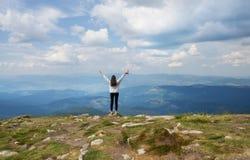 La muchacha se está colocando al borde de la montaña Fotografía de archivo libre de regalías