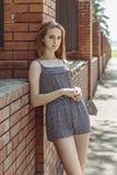 La muchacha se está colocando cerca de una cerca del ladrillo Imagen de archivo libre de regalías