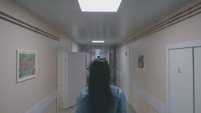 La muchacha se está colocando en el medio de un pasillo del hospital metrajes