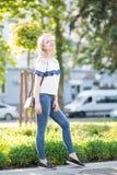 La muchacha se está colocando en una calle de la ciudad Imagenes de archivo