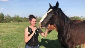La muchacha se está divirtiendo con un caballo que esté pastando en un parque en un prado verde Cerca est? una bici metrajes
