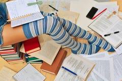 La muchacha se está preparando para aprobar el examen que se sienta en la pila de libros Imagen de archivo libre de regalías