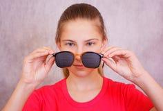 La muchacha se está preparando para intentar encendido entrenar a los vidrios para la corrección de la visión Imágenes de archivo libres de regalías
