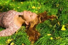 La muchacha se está relajando en la hierba Fotografía de archivo