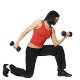 La muchacha se está resolviendo con pesas de gimnasia foto de archivo