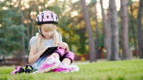 La muchacha se está sentando cerca de la casa, gozando de la tableta Rodado en pcteres de ruedas - en su casco y rodillos almacen de metraje de vídeo