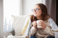 La muchacha se está sentando cerca de la ventana y está sosteniendo una taza blanca blA Imagen de archivo