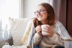 La muchacha se está sentando cerca de la ventana y está sosteniendo una taza blanca blA Imagenes de archivo