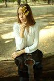La muchacha se está sentando con una guitarra y una hoja del otoño Imagen de archivo