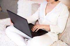 La muchacha se está sentando en casa en el sofá para un ordenador portátil Trabajo en casa Mujer de negocios en casa en el ordena imagen de archivo