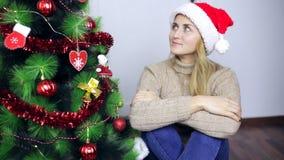 La muchacha se está sentando en el árbol de navidad y la sonrisa almacen de metraje de vídeo