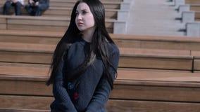 La muchacha se está sentando en el anfiteatro almacen de video