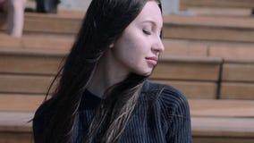 La muchacha se está sentando en el anfiteatro metrajes