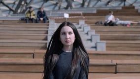La muchacha se está sentando en el anfiteatro almacen de metraje de vídeo