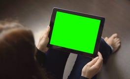 La muchacha se está sentando en el piso con Tablet PC Fotografía de archivo libre de regalías